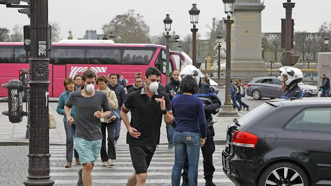 Two joggers wearing protective masks run past a Police officer controlling a vehicle on the Concorde square in Paris, Monday, March 17, 2014. Cars with even-numbered license plates are prohibited from driving in Paris and its suburbs Monday, following a government decision over the weekend. Paris is taking drastic measures to combat its worst air pollution in years, banning around half of the city's cars and trucks from its streets in an attempt to reduce the toxic smog that's shrouded the City of Light for more than a week. (AP Photo/Remy de la Mauviniere)