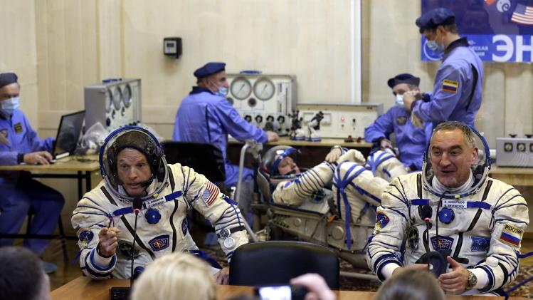Members of the ISS crew, U.S. astronaut Swanson and Russian cosmonaut Skvortsov speak with relatives as Russian cosmonaut Artemyev tests a space suit during pre-launch preparations at the Baikonur cosmodrome