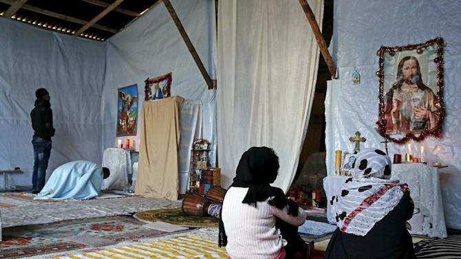 """Christian migrants from Eritrea and Ethiopia pray and read the Bible before Sunday mass at a makeshift church in """"The New Jungle"""" near Calais"""