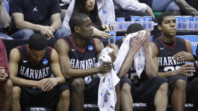 Harvard's Siyani Chambers, Steve Moundou-Missi, Christian Webster and Wesley Saunders (23), from left, sit on the bench at the end of a third-round game in the NCAA men's college basketball tournament in Salt Lake City on Saturday, March 23, 2013. Arizona defeated Harvard 74-51. (AP Photo/Rick Bowmer)