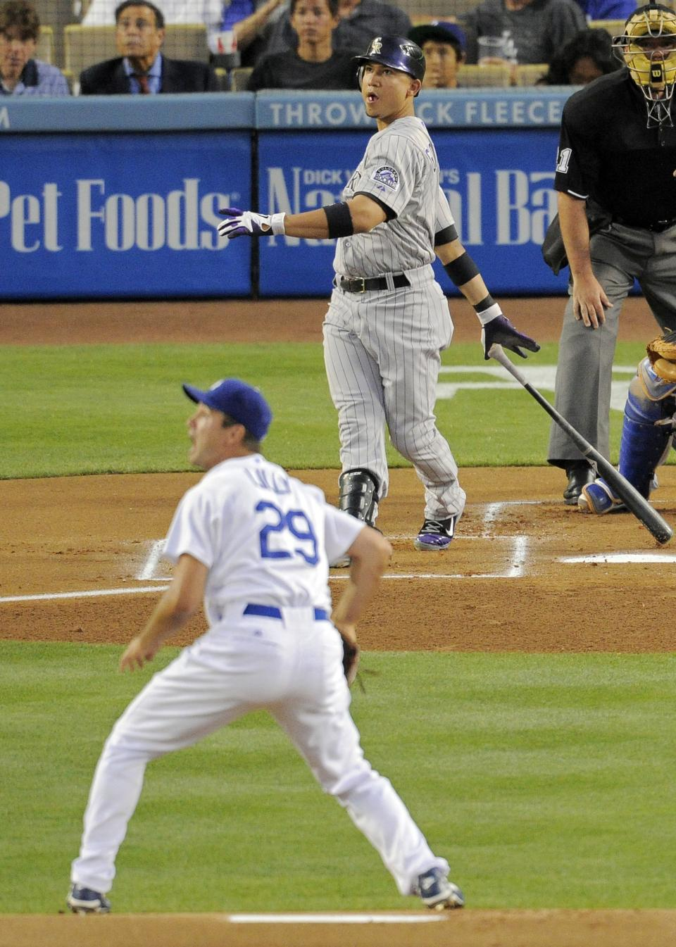 Colorado Rockies left fielder Carlos Gonzalez, top, hits a solo home run as Los Angeles Dodgers starting pitcher Ted Lilly watches it go during the first inning of their baseball game, Friday, Aug. 26, 2011, in Los Angeles. (AP Photo/Mark J. Terrill)