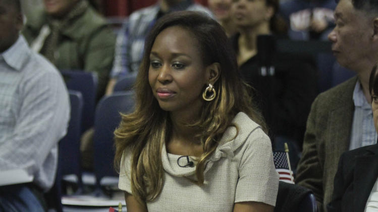 """Immaculee Ilibagiza clutches a small American flag as she listens during a naturalization ceremony at the U.S. Citizenship and Immigration Services (USCIS) on Wednesday, April 17, 2013 in New York. Ilibagiza, the author of the best-seller """"Left to Tell: Discovering God Amidst the Rwandan Holocaust"""" became a naturalized American with 50 other immigrants at a Manhattan ceremony. She survived the 1994 Rwandan genocide that claimed more than a half-million lives. (AP Photo/Bebeto Matthews)"""