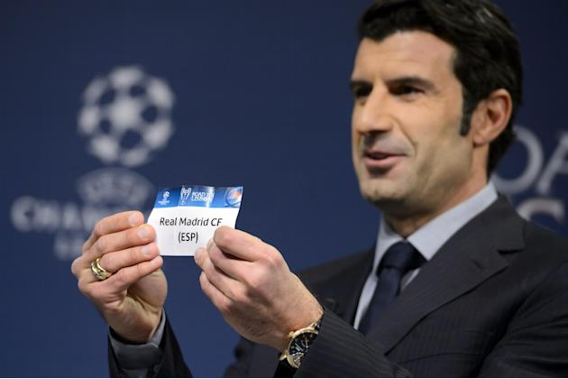 Former Portugal soccer player and Champions League Lisbon final ambassador Luis Figo shows a ticket with Spain's soccer team Real Madrid during the draw of the round of 16 games of UEFA Champions