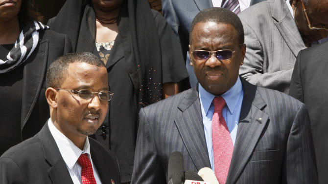 Chairman of the election commission Isaak Hassan, left, speaks to the media after handing over a certificate of the recent election results, a matter of protocol, to Kenya's Chief Justice Willy Mutunga, right, at the Supreme Court in downtown Nairobi, Kenya Monday, March 11, 2013. Uhuru Kenyatta, the son of Kenya's founding father, was named the winner of the country's presidential election on Saturday with 50.07 percent of the vote, but his opponent Raila Odinga refused to concede saying he had plans to petition the Supreme Court, alleging multiple failures in the election's integrity that he said has put Kenyan democracy on trial. (AP Photo/Sayyid Azim)