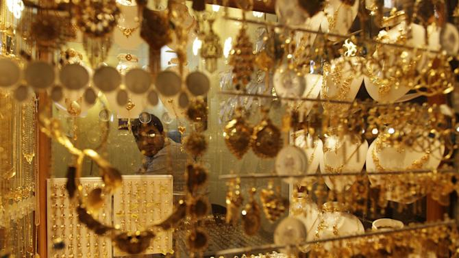 In this photo taken in Tuesday, Oct. 30, 2012, a jeweler waits for customers in Najaf, Iraq. The plunge in Iran's currency is proving bad for business in neighboring Iraq. Fewer Iranians are now able to afford visits to Shiite holy sites here and elsewhere in Iraq because each dollar or Iraqi dinar now costs roughly three times what it did as recently as last year. That has pushed the price of organized tours up sharply and made Iraqi merchants far less willing to accept rials as payment. (AP Photo/Khalid Mohammed)