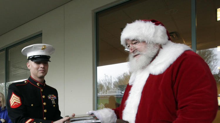 IMAGE DISTRIBUTED FOR CRICKET - A man dressed as Santa, right, and U.S. Marines load boxes full of toys collected by Cricket Wireless for Toys for Tots distribution on Saturday, Dec. 15, 2012 in Glendale, Ariz. (Rick Scuteri/AP Images for Cricket)