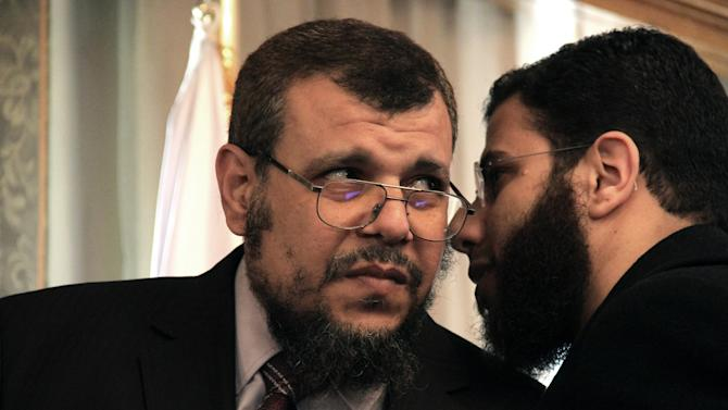 """Khaled Alam Eldin, left, who was fired Sunday from his post as adviser to the Egyptian president for environmental affairs, consults with the Salafist Al-Nour party spokesman, Nader Bakkar during a televised press conference in Cairo, Egypt Monday, Feb. 18, 2013. Alam Eldin broke down in tears while denying he had abused his office and demanded an apology from President Mohammed Morsi calling the firing """"political."""" It is the latest sign of tension between Morsi's Muslim Brotherhood and its Islamist ally ahead of parliamentary elections expected in the coming months. (AP Photo/Mostafa El Shemy)"""