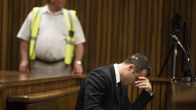 Oscar Pistorius, right, places his hand over his eyes while sitting in court on the fourth day of his trial at the high court in Pretoria, South Africa, Thursday, March 6, 2014. Pistorius is charged with murder for the shooting death of his girlfriend Reeva Steenkamp on Valentine's Day in 2013. (AP Photo/Marco Longari, Pool)