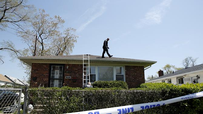 A NYPD officer is seen on the roof of a house while police search house to house for the weapon used to shoot New York City plainclothes police officer Brian Moore at the Queens Village, in New York