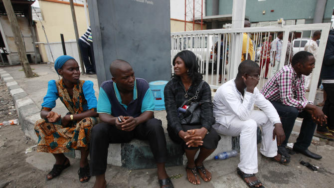 Staff members  of This Day newspaper sit outside, as workers barricaded the  front office due to non payment of salaries  in Lagos, Nigeria, Friday, May 10, 2013. Known more for bringing in celebrities and smiling in photographs next to former Western leaders, a flamboyant Nigerian newspaper publisher now faces a challenge from his most vocal critics _ his own employees. Workers have barricaded the front of This Day newspapers in Lagos, hoping to force publisher Nduka Obaigbena into paying them as much as four months' worth of back salaries due to them. Back pay disputes often hit industries in Nigeria, a country where steady paying jobs remain few, but this crisis has hit a man politically connected to the nation's ruling elite, the second such major business figure to be stung in recent months. (AP Photos/Sunday Alamba)
