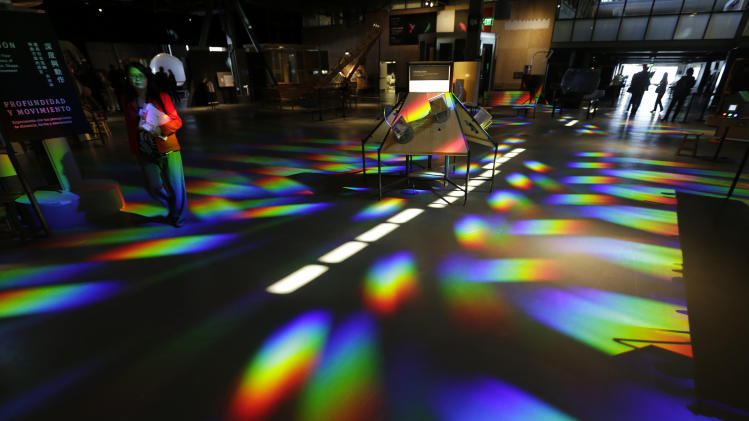 Quynh Tran, left, looks over the colored reflections cast on the floor of the central gallery at the Exploratorium, an interactive science and activities museum, during a preview in San Francisco, Tuesday, April 9, 2013. The new $300 million museum is set to open April 17 at its new location along the bay with more space and new exhibits. The 330,000-square-foot museum at Pier 15 along the Embarcadero has three times more space than the previous location at the Palace of Fine Arts in the city's Marina neighborhood. (AP Photo/Eric Risberg)