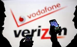 Men are silhouetted against a video screen with Vodafone and Verizon texts as they pose with Blackberry Q10 and Samsung Galaxy S3 in this photo illustration taken in the central Bosnian town of Zenica