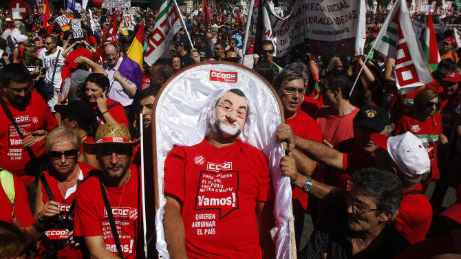 A man performs representing Spanish Prime Minister's Mariano Rajoy dead as a protest against austerity measures applied by the Spanish government, in  Columbus Square in Madrid, Spain, Saturday, Sept. 15, 2012. Tens of thousands of people from all over the country converged on Madrid to hold a large anti-austerity demonstration on Saturday. By mid-morning several major roads had been blocked as buses unloaded protesters at 10 rendezvous points from which marches began. The demonstration was called to protest government cuts during the country's financial crisis. (AP Photo/Andres Kudacki)