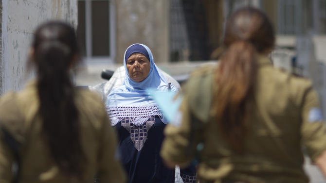 An Arab Israeli woman walks past female Israeli soldiers in Jaffa, a mixed Arab and Jewish part of Tel Aviv, Israel, Wednesday, June 27, 2012. Israel's debate over the court-ordered overhaul of its draft law has veered into turbulent new territory, with politicians considering requiring Israel's Arab citizens to perform community service in lieu of the draft. The proposal has touched a raw nerve among some Israeli Arabs, who say the government shouldn't ask them to shoulder more of the country's burdens while treating them as second-class citizens. (AP Photo/Ariel Schalit)