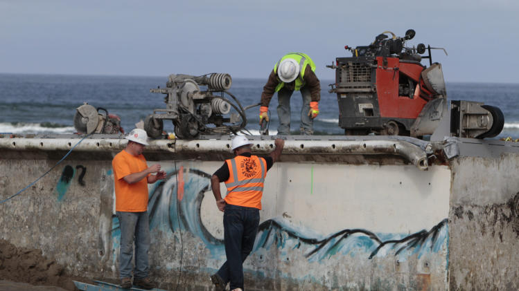 Workers use a cable-cutting system to section the  giant Japanese dock that was torn away by last year's tsunami and washed ashore on Wednesday, Aug. 1, 2012 in Newport, Ore. The plan is to cut the 165-ton concrete dock into five slices, like a loaf of bread, and load them onto flatbed trucks, which drive over the soft sand on a roadway of planks and steel plates. (AP Photo/The Oregonian, Randy L. Rasmussen)  MAGS OUT; TV OUT; LOCAL TV OUT; LOCAL INTERNET OUT; THE MERCURY OUT; WILLAMETTE WEEK OUT; PAMPLIN MEDIA GROUP OUT