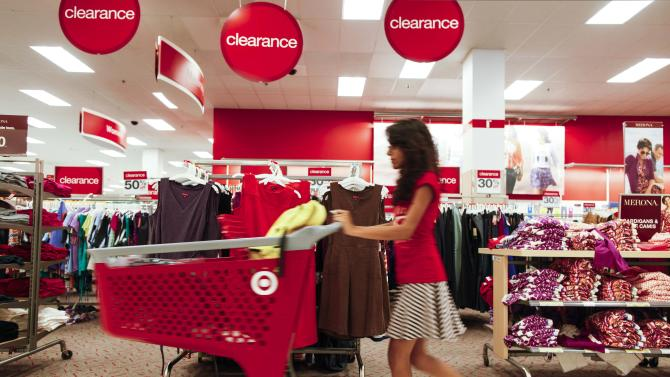 """In this Wednesday, Aug. 22, 2012 photo, a shopper pushes a trolley through the clearance section of a store in Chicago. During the recession, retailers used sales to lure cash-strapped Americans into stores. But that strategy has backfired. It has bred a group of deal junkies that won't shop unless they see """"70 percent"""" signs or yellow clearance stickers. (AP Photo/Sitthixay Ditthavong)"""