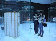 This photo shows visitors looking at items on display at the Louis Vuitton Voyages exhibition in the national museum of China in Beijing, to mark the French fashion house