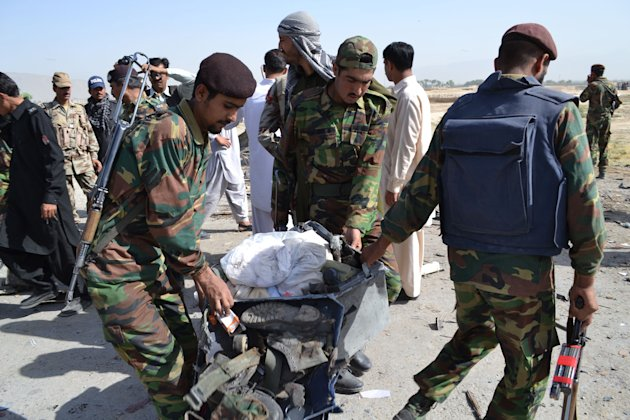 Pakistani security personnel carry a victim's belongings at the site of bombing in Quetta, Pakistan on Thursday, May 23, 2013. A car bomb targeting a police vehicle killed 11 policemen and one civilia