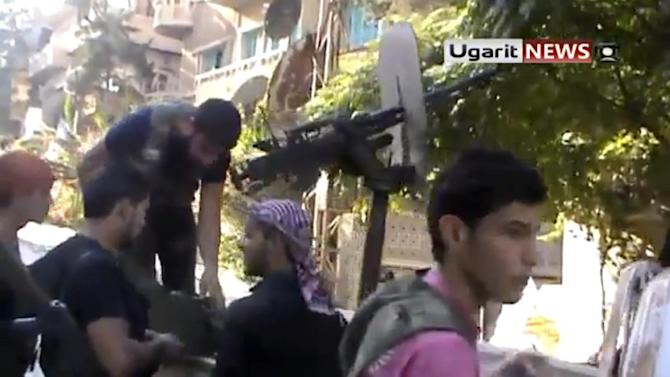 In this image taken from video obtained from Ugarit News, which has been authenticated based on its contents and other AP reporting, Syrian rebels are seen during an operation in Aleppo, Syria, Friday, Sept. 28, 2012. Fighting over Syria's largest city intensified Friday, with the most widespread battles reported there in two months as rebel forces launched a new offensive to rout President Bashar Assad's forces from Aleppo, activists said.(AP Photo/Ugarit News via AP video)