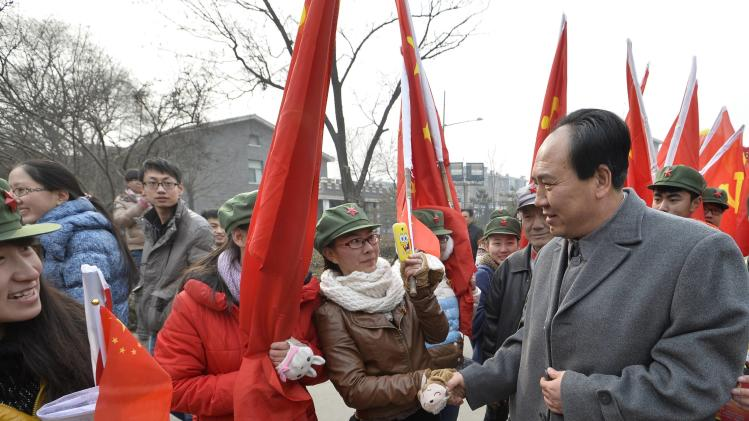 Zhang, who is impersonating China's late Chairman Mao, shakes hands with a college student during a commemorative event ahead of the 120th anniversary of Mao's birth, in Taiyuan