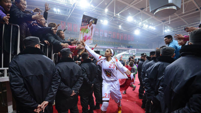 In this Nov. 24, 2012, photo, Shanxi Flame's Maya Moore greets fans as she prepares to take the court for a WCBA basketball game against the Jiangsu Dragons in Taiyuan, China. While her Minnesota Lynx team awaits the return of WNBA training camp in May, Moore is averaging 45 points a game and earning mid-six figures for the Flame, helping bring new fans to the women's game in a baseball crazed nation. (AP Photo/CHINATOPIX)  CHINA OUT