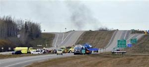 Smoke rises in the distance as firefighters block a highway leading to an area where a train derailed, in the small town of Gainford, Alberta west of Edmonton October 19, 2013. REUTERS/Dan Riedlhuber