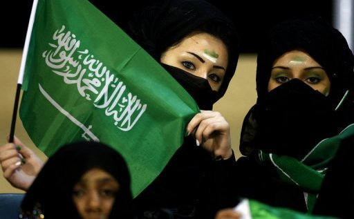 Veiled fans wave Saudi flags as they cheer on their side during a Gulf Cup match against Qatar in 2009. Saudi judoka Wojdan Shaherkani has been banned from wearing the hijab head scarf when she is fighting at the Olympic Games
