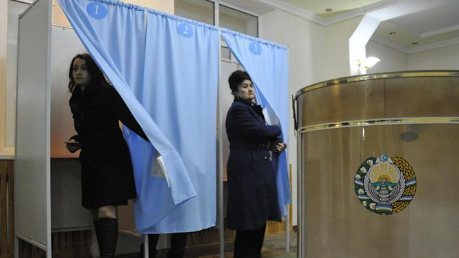 Uzbek citizens leave voting cabins at a polling station in Tashkent, Uzbekistan, Sunday, Dec. 21, 2014. Parliamentary elections are being held in Uzbekistan on Sunday in a vote few observers believe will result in real change.(AP Photo/Anvar Ilyasov)