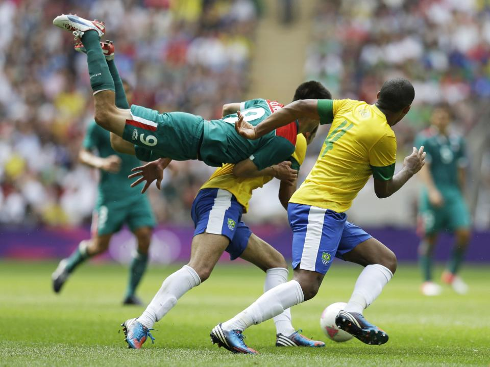 Mexico's Oribe Peralta, middle, goes airborne in front of Brazil's Juan Jesus, right, as they pursue the ball during the men's soccer final at the 2012 Summer Olympics, Saturday, Aug. 11, 2012, in London. (AP Photo/Hussein Malla)