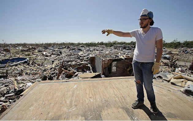 Cody Cannon looks at tornado destruction in his neighborhood from the second floor of his parent's home that once was his bedroom Wednesday, May 22, 2013, in Moore, Okla. Cleanup continues two days af