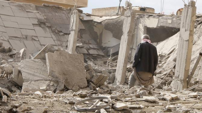 A man makes his way through rubble at a site hit by what activists said were airstrikes by forces loyal to Syria's President al-Assad in Raqqa
