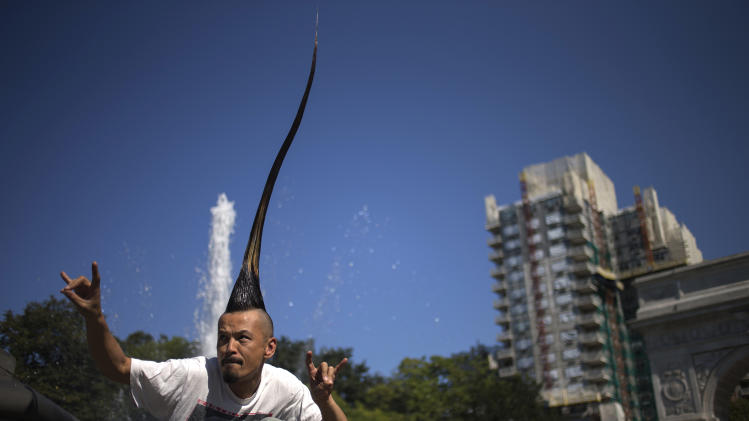 "Japanese fashion designer Kazuhiro Watanabe, who holds the world record for the ""Tallest Mohawk,"" poses for a photographer at a media event in New York"