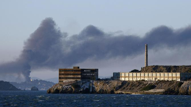 FILE - This Aug. 6, 2012 file photo shows smoke pouring from a fire at the Chevron Richmond Refinery, seen behind Alcatraz Island in San Francisco. The federal government is fighting with itself over a massive fire at a Chevron refinery in California that sent 15,000 people to hospitals with respiratory ailments. In one corner is the U.S. Chemical Safety and Hazard Investigation Board, which conducted 119 interviews in an effort to find out what caused last year's accident and how to prevent it from happening again. In the other is the Environmental Protection Agency, which is conducting a criminal investigation and wants the interviews to help it determine who's responsible. (AP Photo/Eric Risberg, File)
