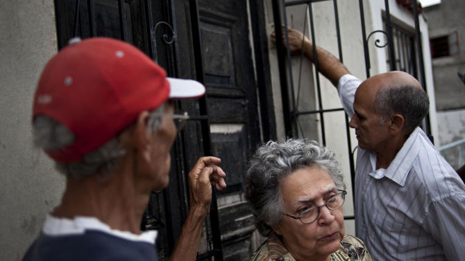 Aida Valdes, center, member of the Christian movement of liberation talks to reporters as neighbors arrive to the house of Oswaldo Paya in Havana, Cuba, Sunday, July 22, 2012. Paya died in a car crash. He was 60 years old. Dissident Elizardo Sanchez says he confirmed Paya's death on Sunday with associates in the city of Bayamo, 500 miles (800 kilometers) east of the capital. (AP Photo/Ramon Espinosa)