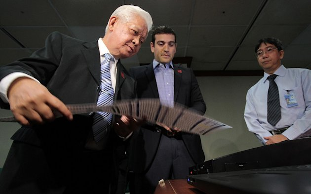COMELEC Chairman Sixto Brillantes inspects Smartmatic's Precinct Count Optical Scan (PCOS) with Smartmatic Asia Pacific President Cesar Flores and Atty. Himerio Garcia Committee Secretary during the presentation of the accuracy of the PCOS machines. (Joseph Vidal / Senate Pool / NPPA Images)