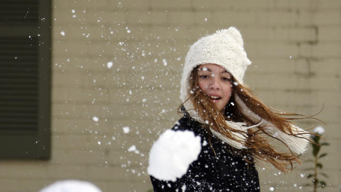 Skylar Alexander, 11, tosses a snowball at her brother Parker Alexander, 14, outside their Jackson, Miss., home, Thursday,  Jan. 17, 2013.  A winter storm system left 2 to 4 inches of snow in parts of central Mississippi before heading east toward Alabama, the National Weather Service said. (AP Photo/Rogelio V. Solis)