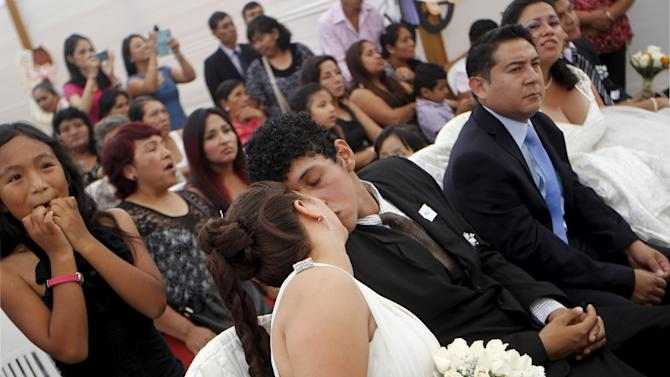 A couple kisses during a mass wedding ceremony ahead of Valentine's Day celebrations in Lima