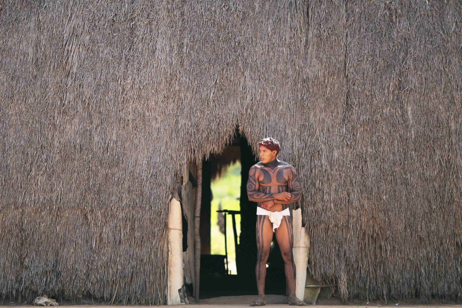 A Yawalapiti man walks out of a hut in the Xingu National Park