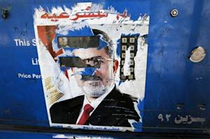 The remnants of a poster of ousted Egyptian President Mohamed Mursi are seen at a petrol station in Cairo