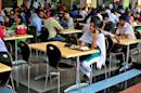 An employee speaks on a mobile phone as she eats her lunch at the cafeteria in the Infosys campus in Bengaluru