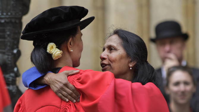 "A friend, name not available, embraces Myanmar opposition leader Aung San Suu Kyi, following an award ceremony at the Oxford University, Oxford, England, on Wednesday, June 20, 2012.  It was a long wait, but Aung San Suu Kyi has finally received her honorary degree from Oxford University. In her speech, Suu Kyi praised the role Oxford played in helping her see humankind at its best during her long years under house arrest in Myanmar. ""The most important thing that I learned was respect for all of civilization,"" she said, wearing a traditional red gown. ""In Oxford I learned to respect all that is best in human civilization. That helped me cope with something that was not quite the best."" (AP Photo/Lefteris Pitarakis)"