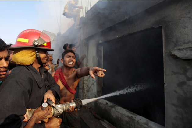 Bangladeshi firefighters and volunteers work to douse a fire at a two-storied garment factory in Dhaka, Bangladesh, Saturday, Jan. 26, 2013. The fire swept killed at least six female workers and injur