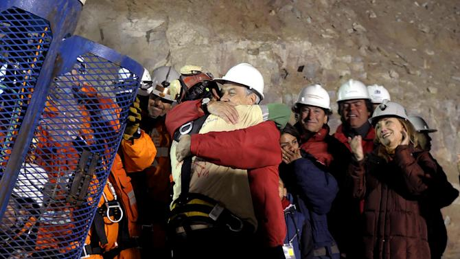 In this photo released by the Chilean presidential press office, Chile's President Sebastian Pinera, front right, hugs rescued miner Florencio Avalos after Avalos was rescued from the collapsed San Jose gold and copper mine where he was trapped with 32 other miners for over two months near Copiapo, Chile, Tuesday Oct. 12, 2010.  (AP Photo/Jose Manuel de la Maza, Chilean presidential press office)