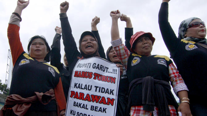 "In this Friday, Dec. 21, 2012 photo, Indonesian women shout slogans during a protest demanding District Chief Aceng Fikri to step down, in Garut, West Java, Indonesia. The Supreme Court late last month recommended that the president dismiss Fikri for violating the marriage law, following a public outrage after he divorced his second teenage wife by text message just four days after their wedding. The response has been seen as a small step forward for women's rights in the secular country where most people practice a moderate form of Islam. The writings on the poster reads ""Garut District Chief must step down or there will be no more virgins."" (AP Photo/Kusumadireza)"