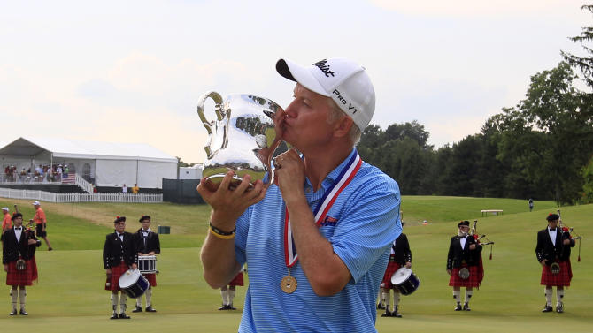 Roger Chapman kisses the Francis D. Ouimet Memorial Senior Open Championship Trophy after winning the U.S. Senior Open at the Indianwood Golf and Country Club in Lake Orion, Mich., Sunday, July 15, 2012. (AP Photo/Carlos Osorio)