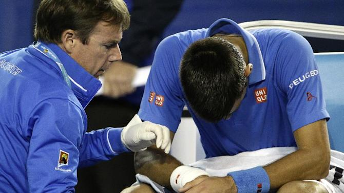 Novak Djokovic of Serbia, right,  receives treatment as he plays Andy Murray of Britain during the men's singles final at the Australian Open tennis championship in Melbourne, Australia, Sunday, Feb. 1, 2015.(AP Photo/Bernat Armangue)