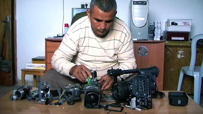 "This undated publicity photo released by Kino Lorber, Inc. shows Co-director Emad Burnat with his five broken cameras. Burnat and Guy Davidi co-directed the documentary film, ""5 Broken Cameras."" (AP Photo/Kino Lorber, Inc.)"