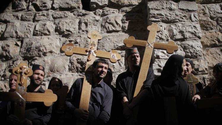 Christian worshippers hold crosses during a procession along the Via Dolorosa on Good Friday in Jerusalem's Old City