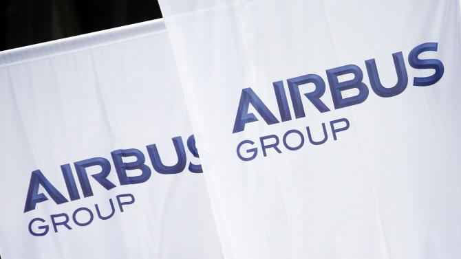 Flags with the new logo of aircraft manufacturer Airbus Group are seen on the entrance gate of the company's office building in Paris