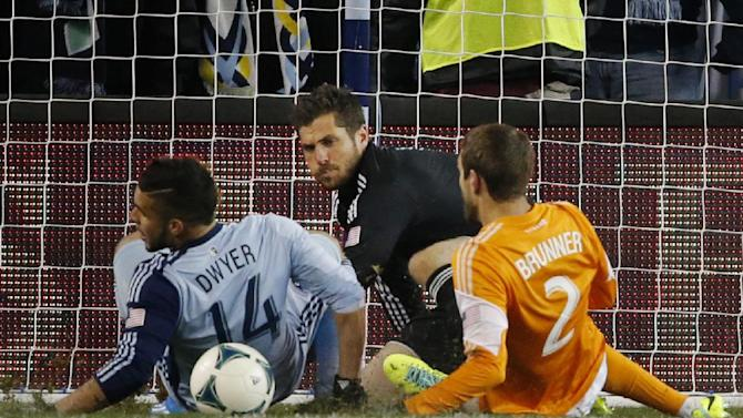 Houston goalkeeper Tally Hall, back, covers while Sporting KC forward Dom Dwyer (14) and Houston defender Eric Brunner (2) work in front of the net during the first half of an MLS playoff soccer match in Kansas City, Kan., Saturday, Nov. 23, 2013